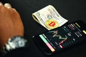 A single Bitcoin on top of cash next to a mobile phone